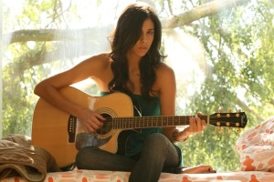 Selena Garcia playing acoustic guitar